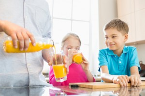Midsection of father serving orange juice for children in kitchen