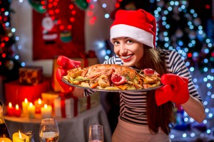 Smiling woman with turkey garnished with potato and garnet dressed with Christmas hat on festive light background