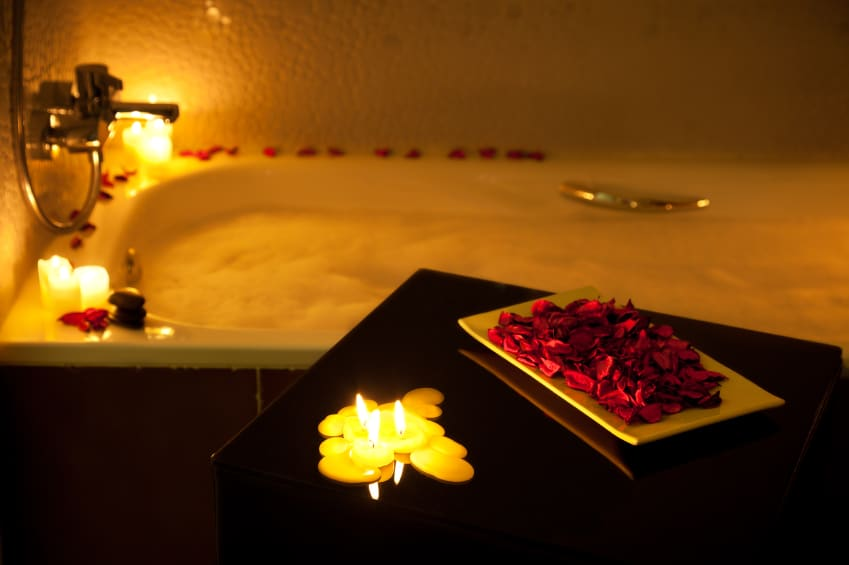 Romantic bathtub ready with candlelight and red petals