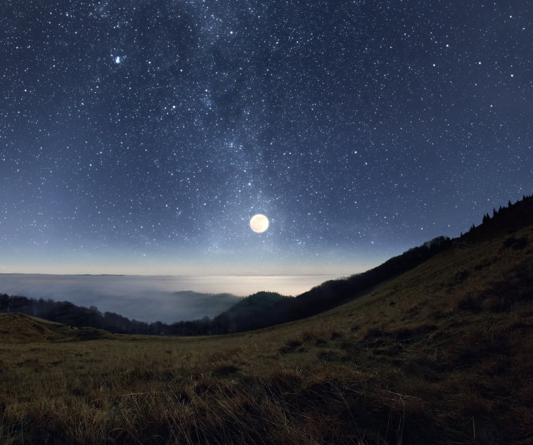 Starry night sky with rising full moon over the misty mountains