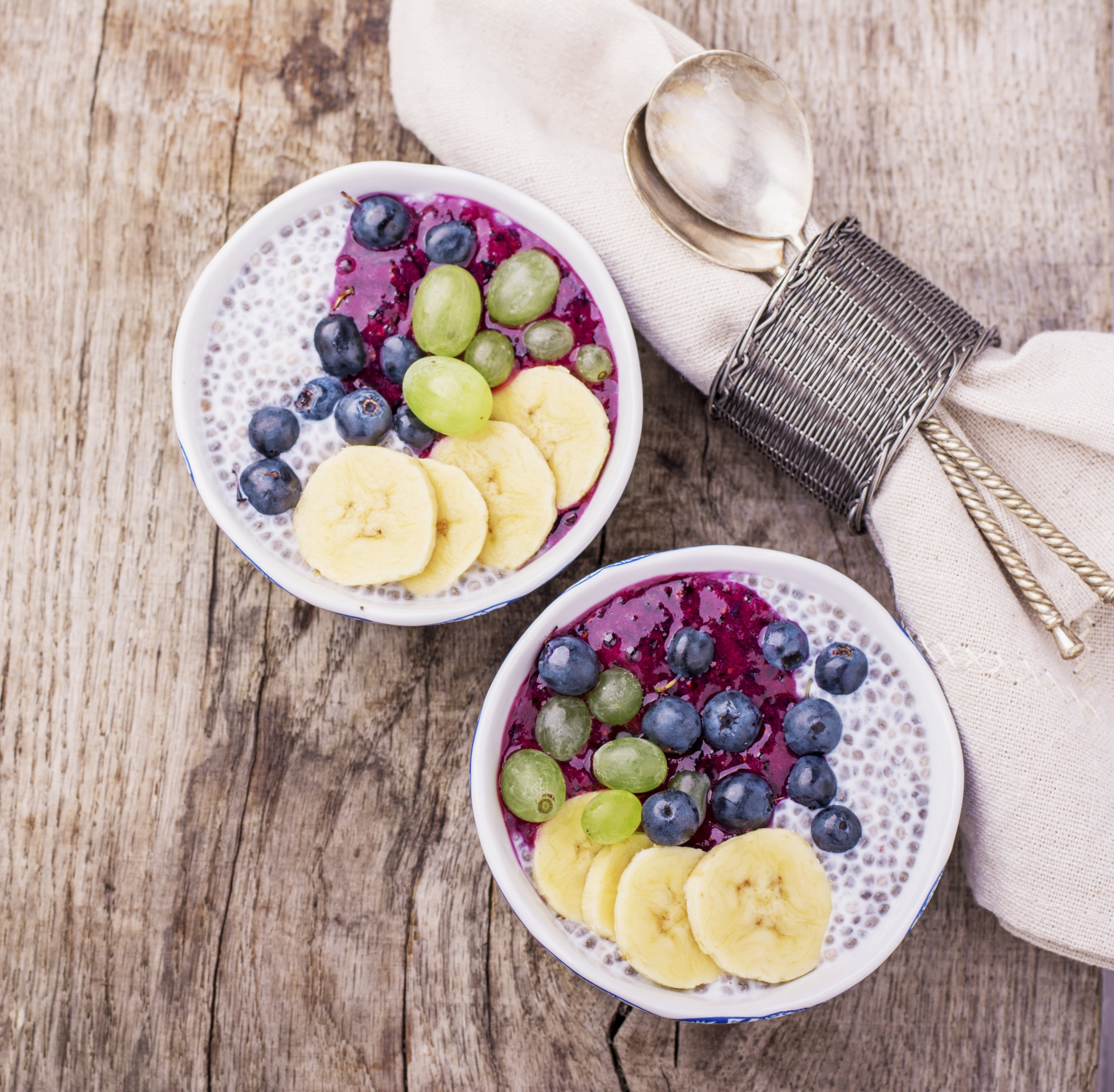 Chia Pudding for breakfast in bowls garnished with berry smoothies, grapes, petals of almond and blueberry in two portions on a wooden background with a napkin and spoon. Top view. selective Focus