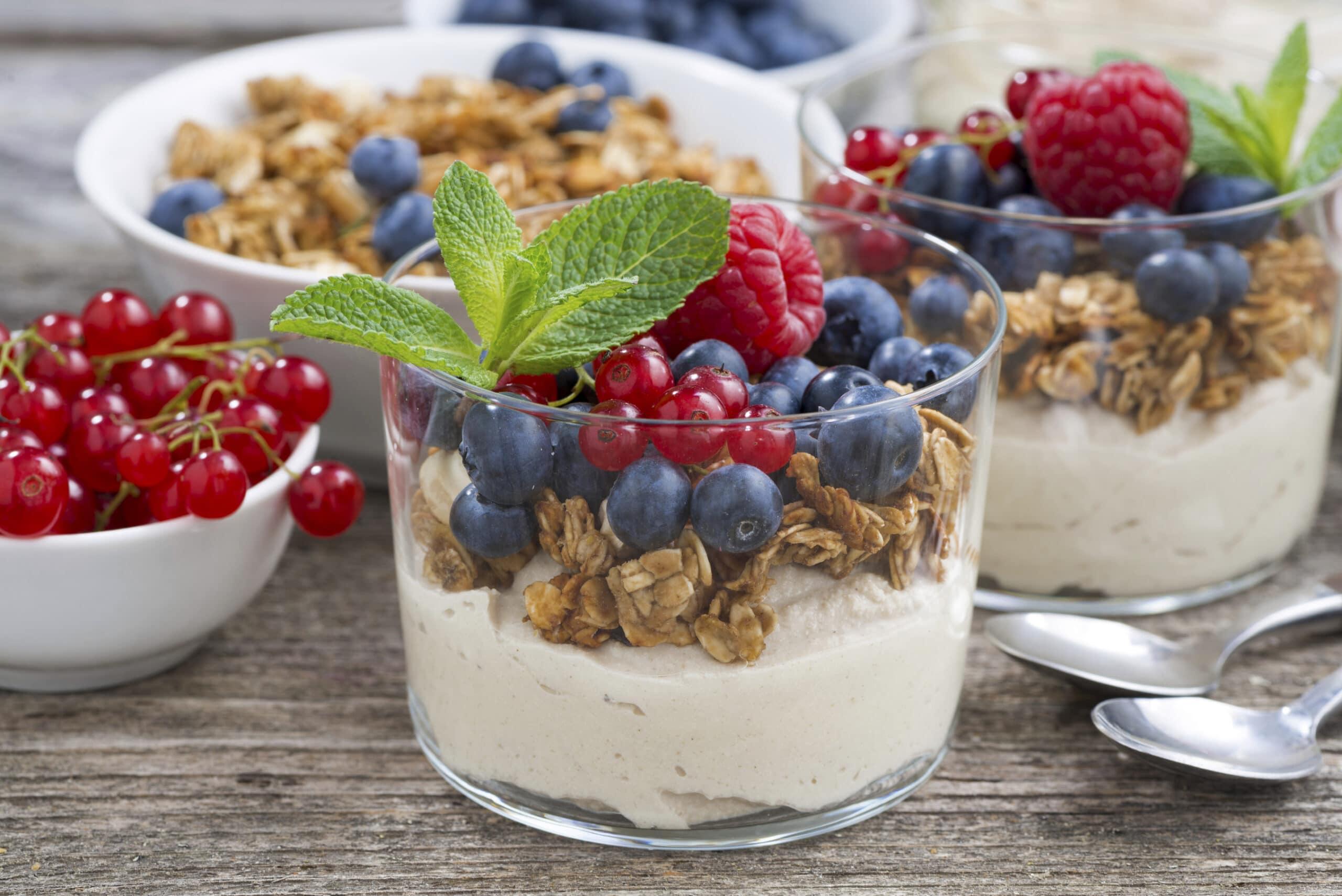 dessert with sweet cream, fresh berries and granola, closeup, horizontal