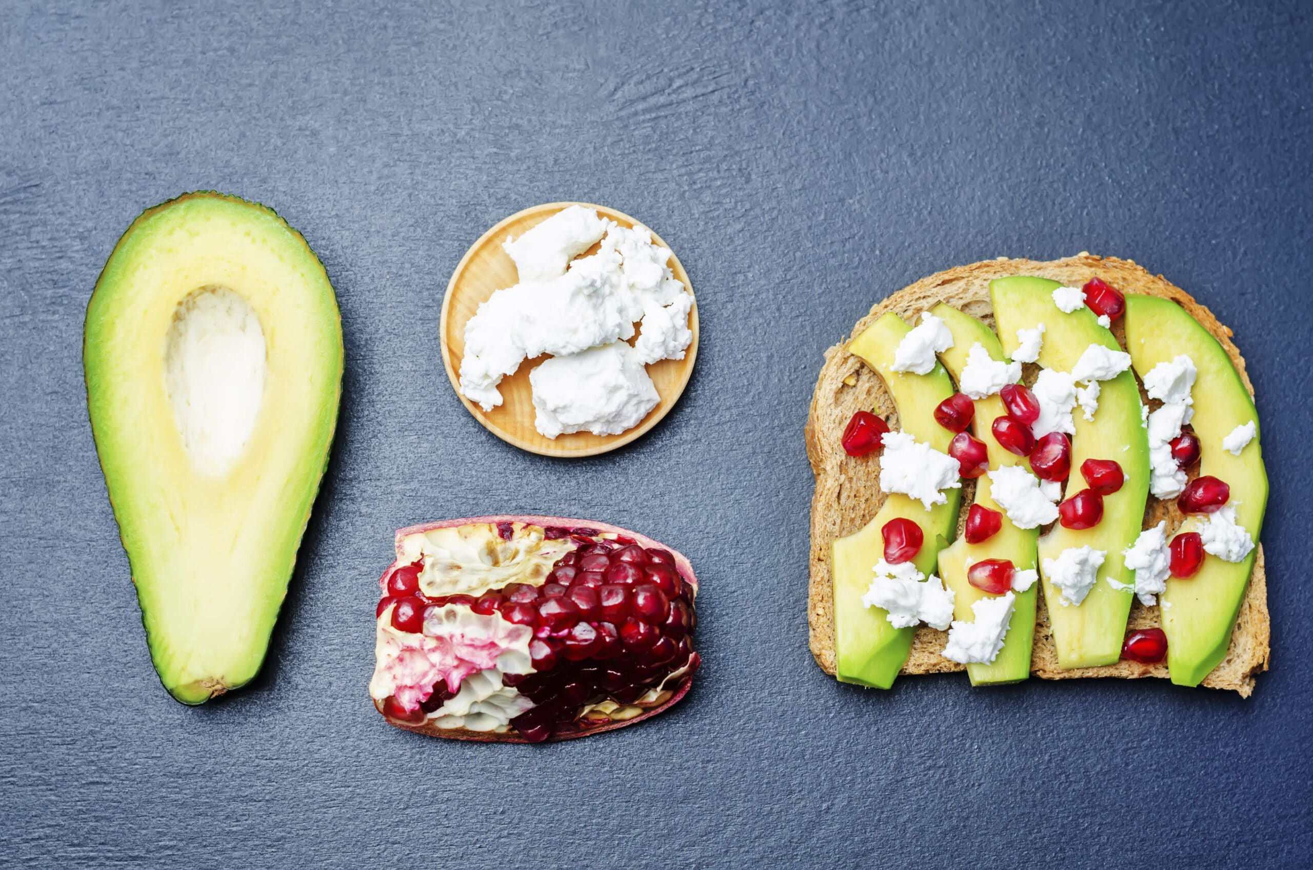 Sandwich with avocado, feta and pomegranate on a black background. toning. selective focus